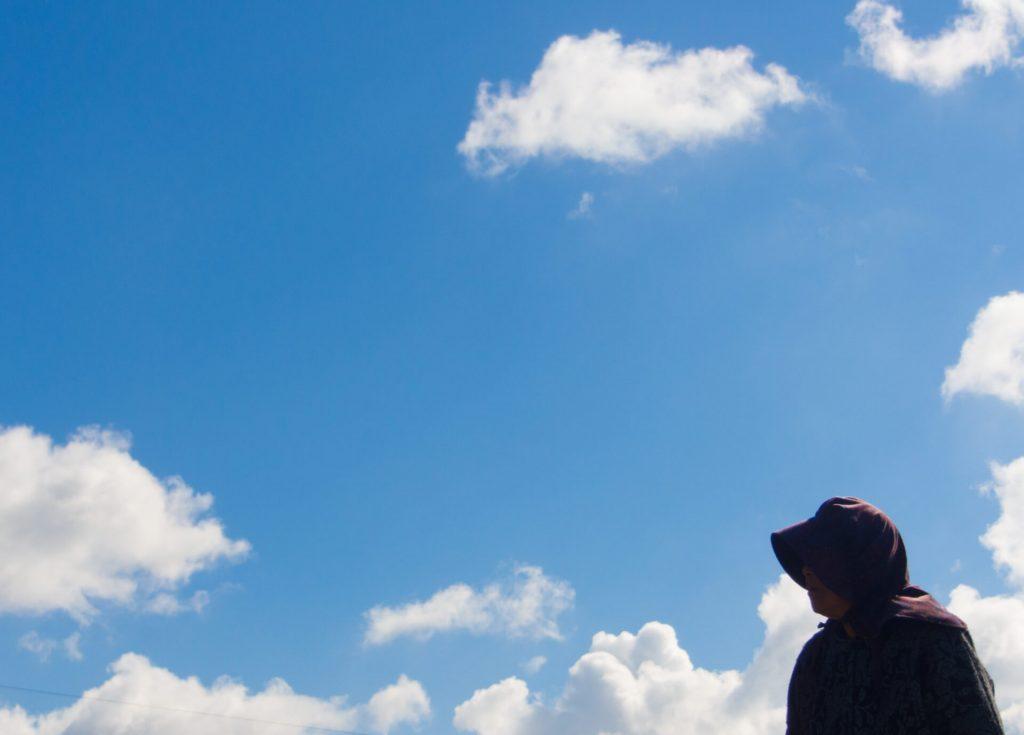 広い青空の下に立っているおばあちゃんのシルエット