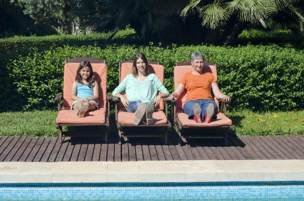 祖母・母・娘の女性3代がプールサイドでデッキチェアに座っている写真