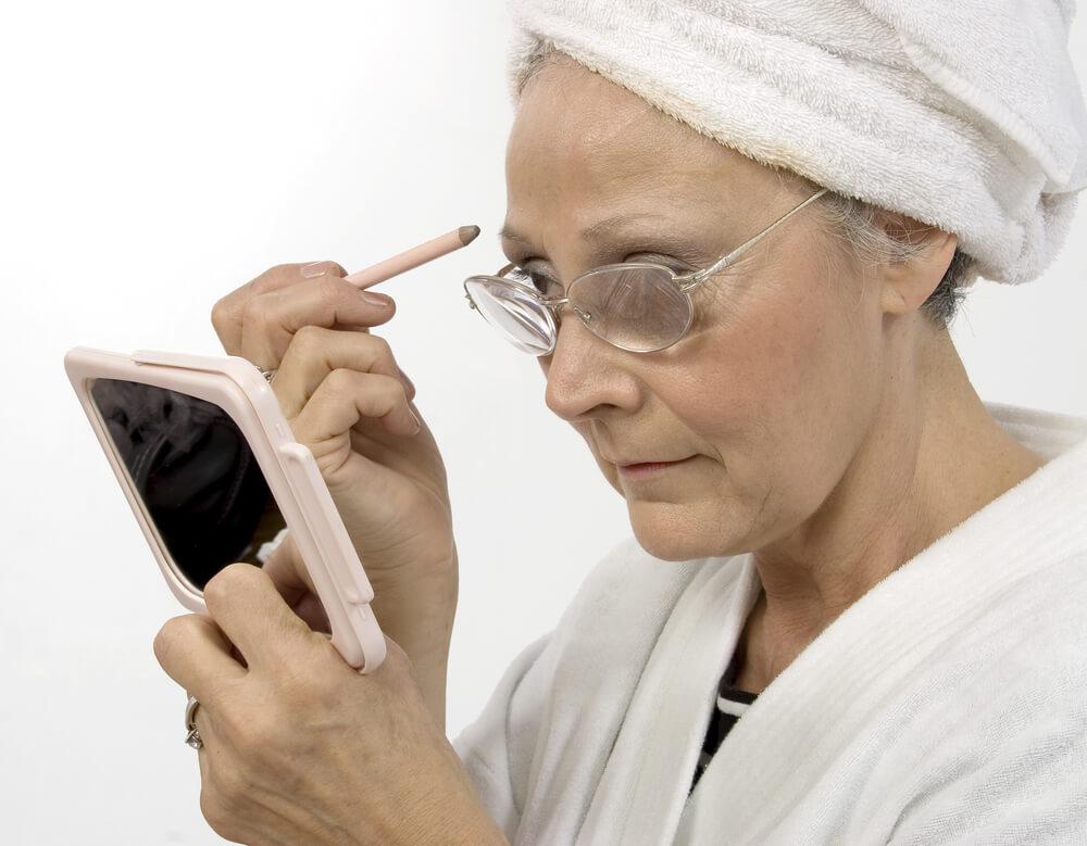 老眼鏡をかけて鏡を見ながら眉を描いている女性