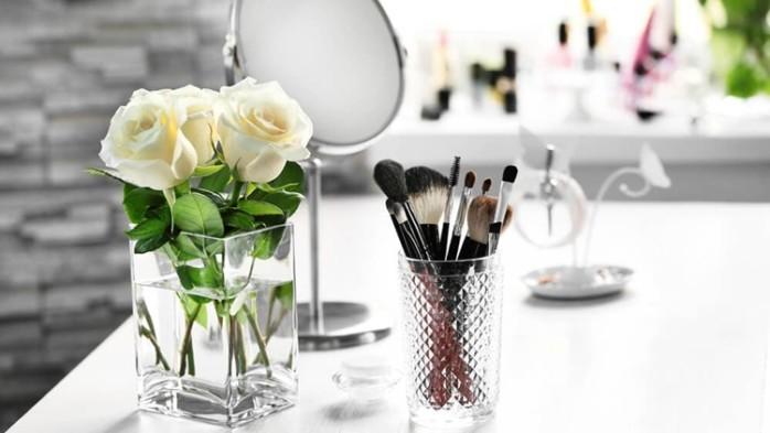 花瓶の花とビンに入ったメイクブラシ