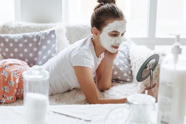 ソファーで寛ぎながら女の子がクレイマスクをして鏡を見ている